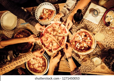 Top view of friends taking a slice of pizza and eat dinner together in friendship -  table top view from above