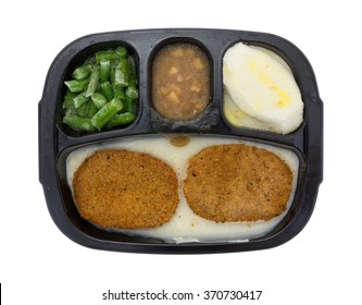 Top view of a frozen fried chicken patties TV dinner with potatoes, green beans and apples in sauce on a white background.
