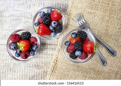 Top view of fruit salad in small transparent bowls on wooden table
