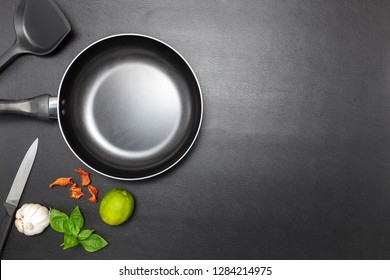 Top view frying pan on black leather table background.