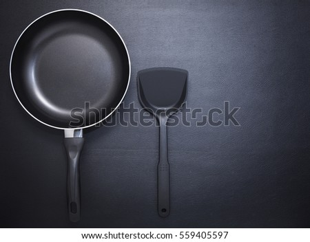Top view frying pan and plastic spade on black table background