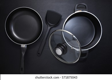 Top view frying pan and pot on black table