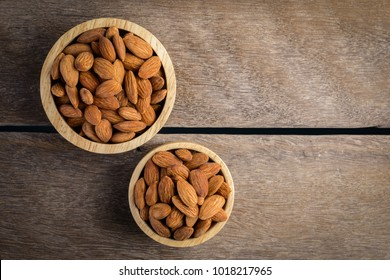 Top view of Full of Almonds in wooden brown bowl on wooden background