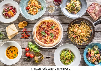 Top of view full table of italian meals on plates and pan. Pizza pasta risotto soup and fish vegetable salad.