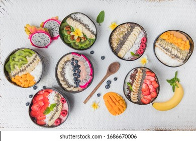 Top view, full table with vegan smoothie bowls with fruits and seeds
