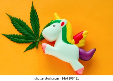 top view funny cute unicorn with marijuana green leaf on a vibrant yellow background