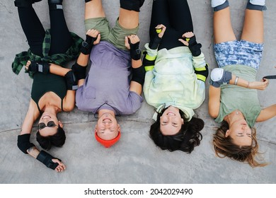 Top view of funny four skaters chilling on a concrete paving at skatepark. Wearing some protective gear. Legs up. High angle view.