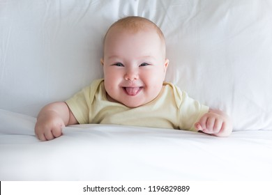 top view of funny little baby girl lying on the bed under blanket with copy space