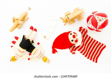 Top view of funny vintage children toys on white background. Assortment consists of a clown, dolls, a wooden grasshopper, a wooden snail and a ball.