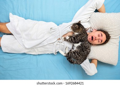 Top view of funny young guy in white bathrobe lying with mouth opened on bed while cat sleeping on male neck