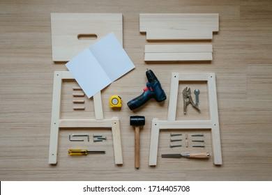 Draufsicht auf die Möbelmontage Teile und Werkzeuge auf Holzfußboden für DIY tun es selbst und montieren Sie die Arbeit, leere Raumanleitung Papier, um das Logo zu setzen