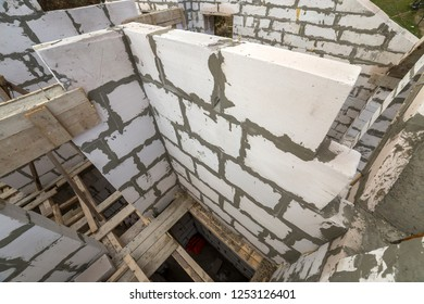 Top view of future cottage energy saving walls of large white hollow foam insulation blocks and temporary wooden scaffolding frame. Construction and masonry, modern building technology concept.