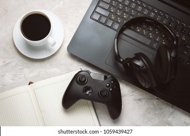Top view of Gamepad, Laptop and Headphones, Cup with Coffee and Notebook on a White table with copy space. Gamers background concept.