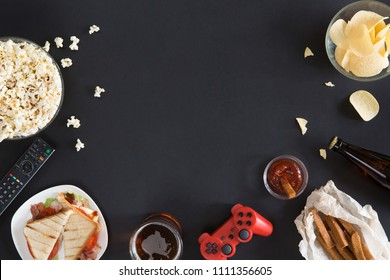 Top view of gamer accessorises and snacks frame, flat lay on black background with copyspace. Joystick and gamepad, keyboard, game console, mouse, mobile phone, beer, chips and popcorn.