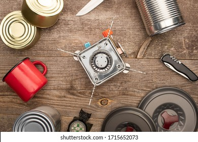 top view of gas burner, tin cans, metal cup,  on wooden table
