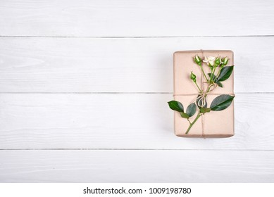 Top view of gift box with branch of fresh roses on wooden table, copy space. Holiday background, sale, shopping. Gift wrapping. Greeting card for Valentines Day, Womans Day, Mothers Day, flat lay