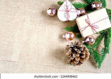 Top view gift box hand made with brown paper tight with red ans white ribbin, green leaf of pine tree and brown fruit with  small christmas ball put on tissue , christmas background .