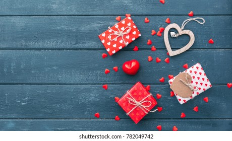Top view of gift box with and red hearts decorations on Valentines day over wooden background