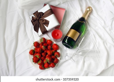 Top view gift box strawberry and bottle of champagne , romantic morning surprise breakfast in bed