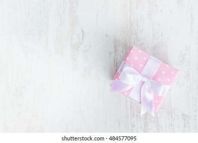 Top view of a gift box wrapped in pink dotted paper and tied satin bow over a white wood background.