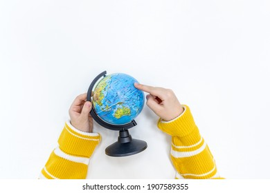 Top view of a girl hand holding a globe in Montessori school. The concept of using the resources of the planet earth for teaching children geography.