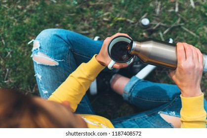 Top view girl holding in hands cup of hot tea on green grass in outdoors nature park, beautiful woman hipster enjoy drinking cup of coffee thermos, lifestyle relax recreation meditation concept