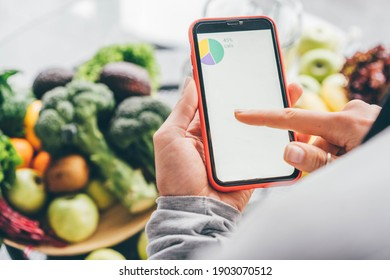 Top view of girl holding smartphone with calorie counting app on kitchen table near fresh vegetables.