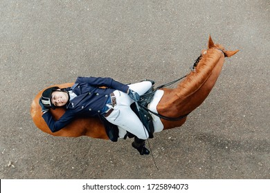 Top view of a girl lies on a horse. Dressage equestrian contest