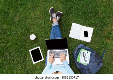Top view of girl sitting in park with laptop, tablet, smartphone, backpack and coffee. Copy space on screens. Flat lay