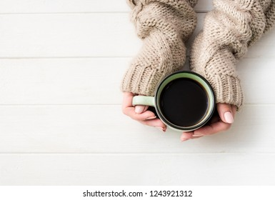 Top view of girl in sweater holding coffee mug on white table