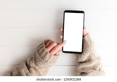Top view of girl in sweater using smartphone on white table background