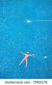 Top view of girl swimming in the pool.