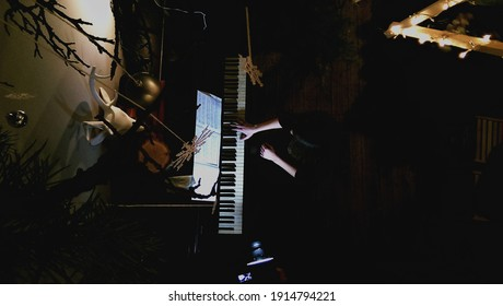 Top view of girl who plays on piano in the room with Christmas decorations in Odessa, Ukraine