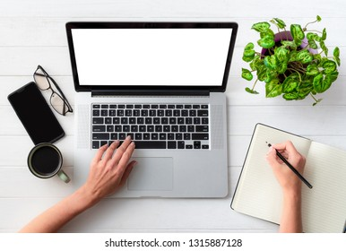 Top view of girl working on laptop and writing at working place