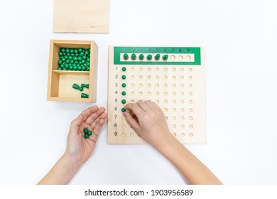 Top view of girls hand is playing and sorting a puzzle of colored plastic beads in montessori school. Concept of using a mathematical geometry learning resources for children education.