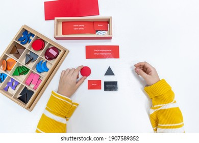 Top view of girls hand is playing and sorting a puzzle of colored wooden geometric shapes in montessori school. Concept of using learning resources for children education language and writing.