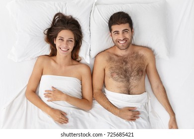 Top view of glad positive family couple has unforgettable night togehter, romantic relationship, smile happily, lie in white comfortable bed, enjoy togetherness and good atmopshere at bedroom