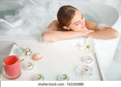 Top view of glad young woman pampering her body in water. She is leaning on bathtub side and smiling. Candles and flowers are on table