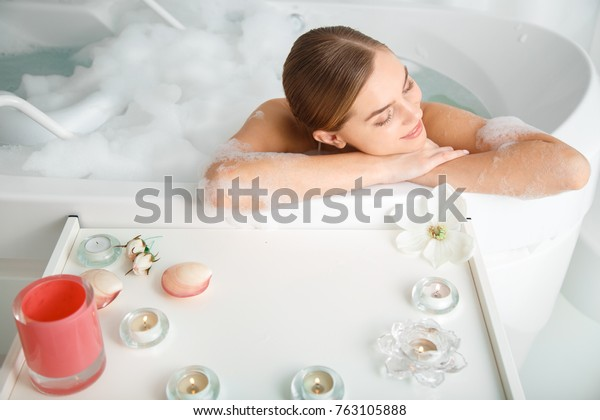 幸せな若い女性の上からの眺めは、水の中で彼女の体を甘やかしている。彼女は浴槽の側に寄りかかって微笑んでいる。ろうそくと花がテーブルの上にある