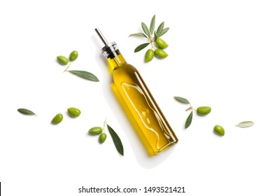 Top view of glass bottle with olive oil and green olives with leaves isolated on white background.