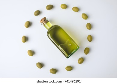 Top view of glass bottle with olive oil inside of olives circle isolated on white