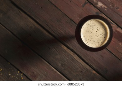 Top view of a glass of cold dark beer placed on a rustic wooden table