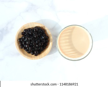 Top view of a glass cup of pearl milk tea (also called bubble tea) and a plate of tapioca ball. Pearl milk tea is the most representative drink in Taiwan. Taiwan food . With copy space.
