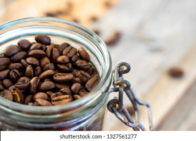 Top view of a glass jar filled with coffee beans on rustic wooden boards
