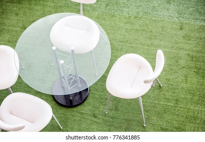 Top view of glass tables and white chairs on green background in modern office