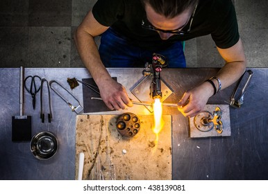 Top View of Glassblowing Professional Working on a Torch Flame with Glass Tubes (focus on the tools)