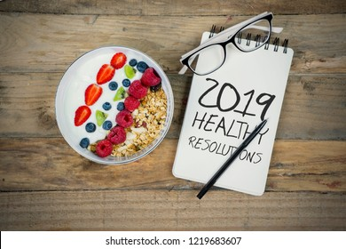Top view of glasses, pen, and text of 2019 healthy resolutions on paper notes with cereals over table