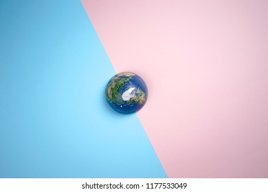 Top view of globe on pastel background