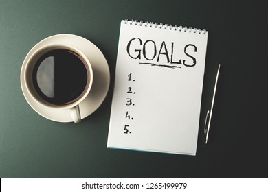 Top view of GOALS list on notepad on dark table, business success inspiration and motivation concept, vintage toned