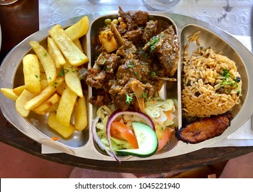 Top view of Goat Stew lunch from the Curacao island. Completed with french fries and rice and beans.